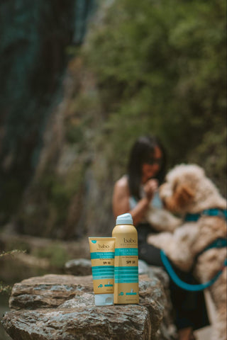 Girl on a hike with her dog wearing sport sunscreen