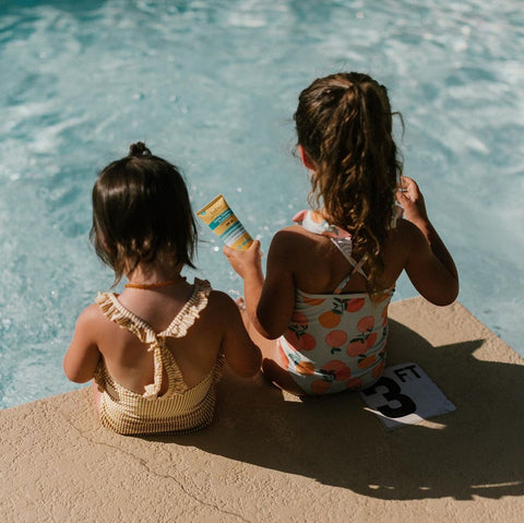 two young girls at the pool wearing sport sunscreen