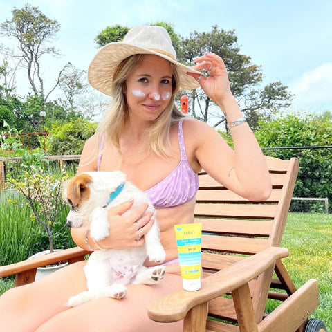 Woman holding her dog outside while wearing sport sunscreen