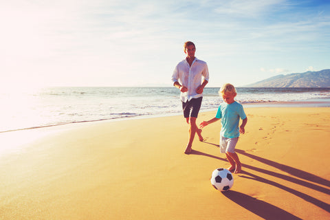 Parents and kid playing soccer while wearing spray sunscreen