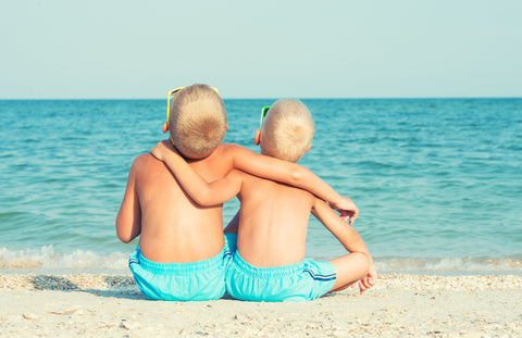 siblings hugging while sitting on the beach