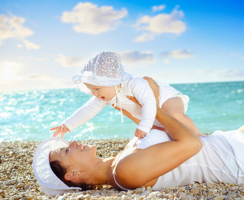mom laying on beach with baby