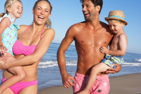 Happy family at the beach that has sunscreen protection