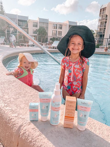 Two kids at the pool with the essential Babo Botanicals sun protection products