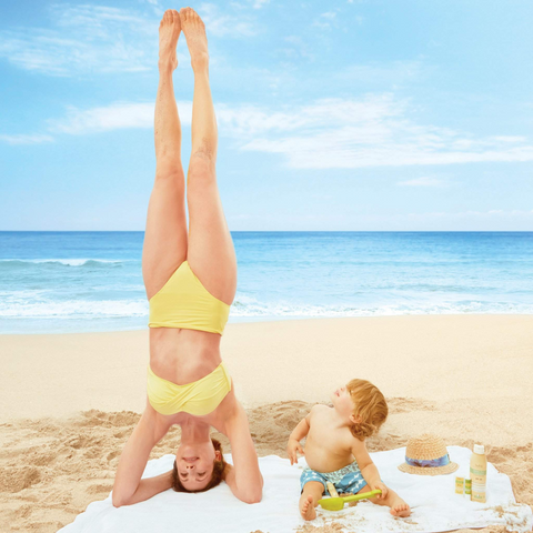 Mom doing handstand on beach while child is watching