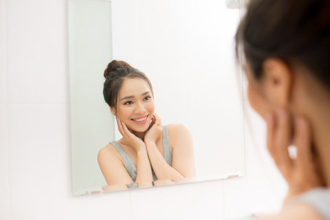 Woman smiling while looking at her face in the mirror