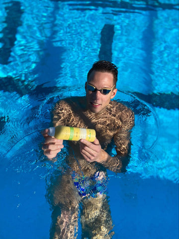Swimmer in pool holding a bottle of spray sunscreen