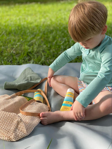 Child outside on a picnic with the sun care essentials