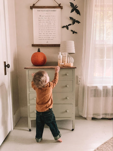 Little boy in his terrible twos grabbing something from the night stand