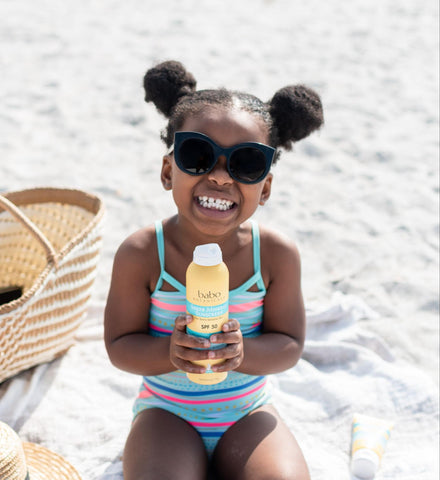 Young girl at the beach holding babo botanicals sun spray