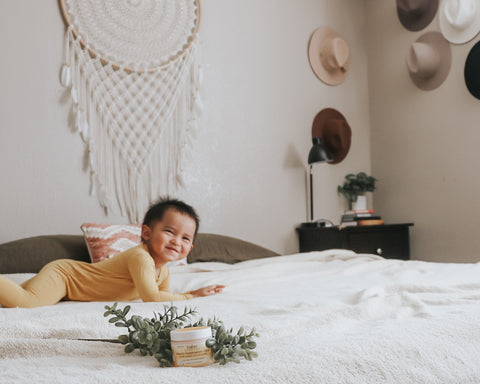 Young kid on bed smiling while parents are deciding when do kids stop napping