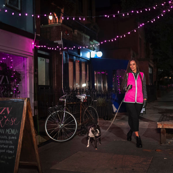 Brooklyn street at night beautiful woman walking dog in a designer mohair reflective vest parked bicycle pink lights