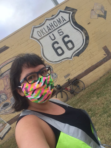 Christina Watanabe selfie in front of Route 66 mural wearing a vespert reflective vest