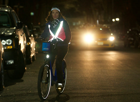 woman riding a bicycle at night wearing a vespert reflective vest reflective hat reflective shoelaces