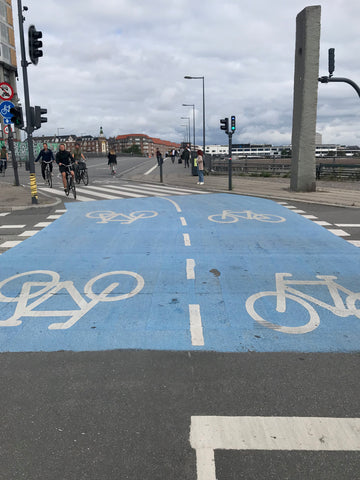 Bold blue two-way bike lane painted on the street in Copenhagen Denmark with white bicycles