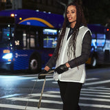 Beautiful woman dog walking  at night. She wears a  high fashion grey silver color mohair reflective safety vest