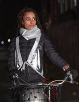 beautiful woman with braids and a bicycle with her helmet in the bicycle basket models silver lamé hi vis chic reflective safety vest and silver grey reflective Mohair scarf reflective fashion for cycling bicycling walking dog walking and being seen day and night
