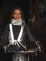 On a Brooklyn Brownstone lined street at night beautiful woman with braids and a bicycle with her helmet in the bicycle basket models silver lamé hi vis chic reflective safety vest and silver grey reflective  Mohair scarf reflective fashion for cycling bicycling walking dog walking and being seen day and night