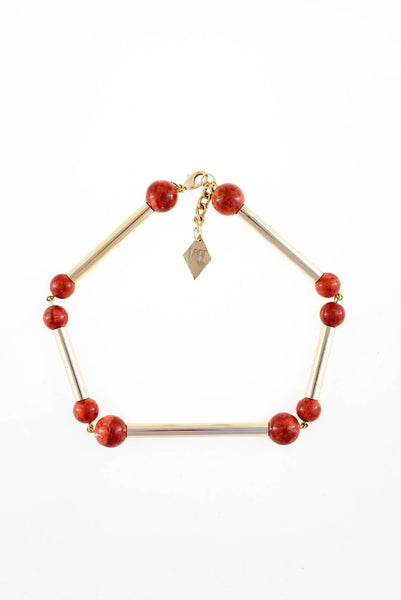 The Bonbon necklace made of warm red coral (gold edition) and cold brass, which was hand-cut and galvanized.