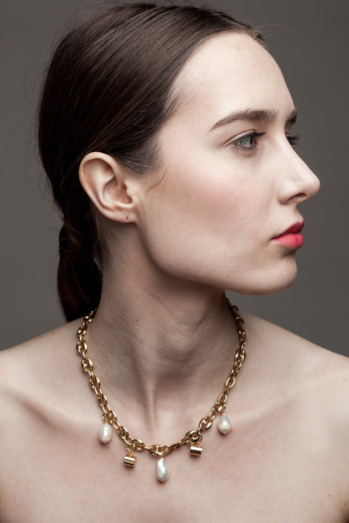 This necklace features 24K gold-plated chain called coffee beans chain and hand cut and 24K gold-plated brass and freshwater pearls.