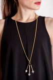 The Elsa necklace is composed of beautiful rutilated quartz, onyx beads and hand-cut and galvanized brass.