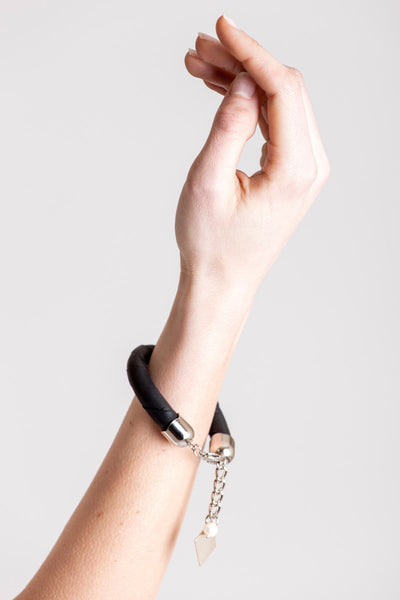 The no. 10 edition of the handcuff bracelet is made of black leather with galvanized metal components and river pearl. Silver edition.