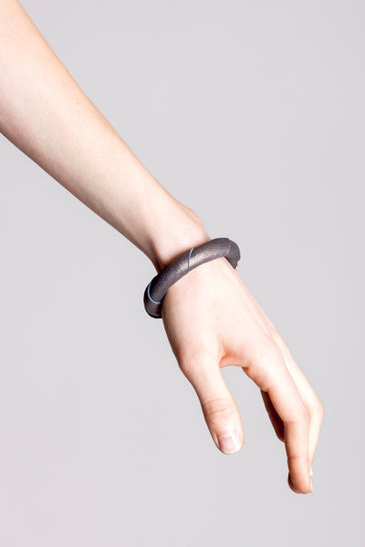 The no. 14 edition of the handcuff bracelet is made of leather in copper color with galvanized metal components. Gold edition.