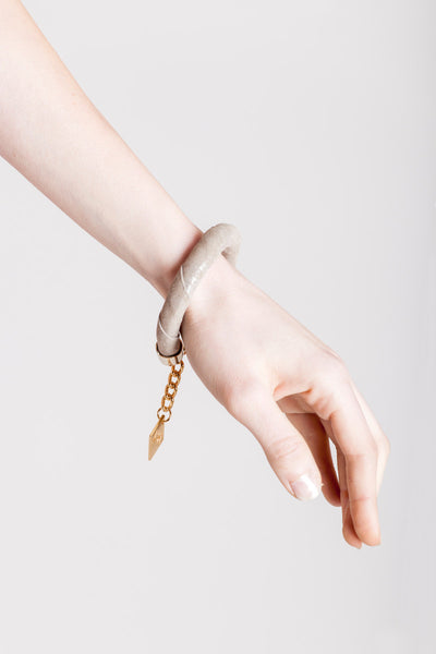 The no. 15 edition of the handcuff bracelet is made of beige suede with silver details and galvanized metal components. gold edition.