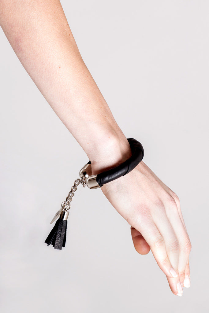 The no. 4 edition of the handcuff bracelet is made of black leather with galvanized metal components and leather tassel. Silver edition. Silver edition.