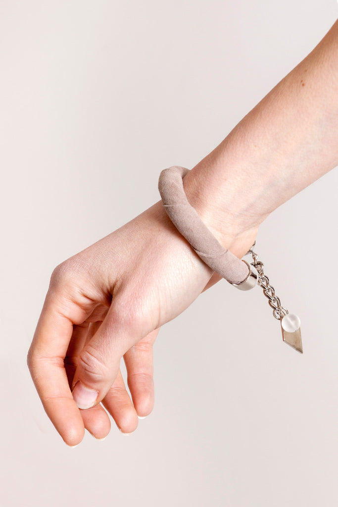The no. 5 edition of the handcuff bracelet is made of beige suede with galvanized metal components. Silver edition.