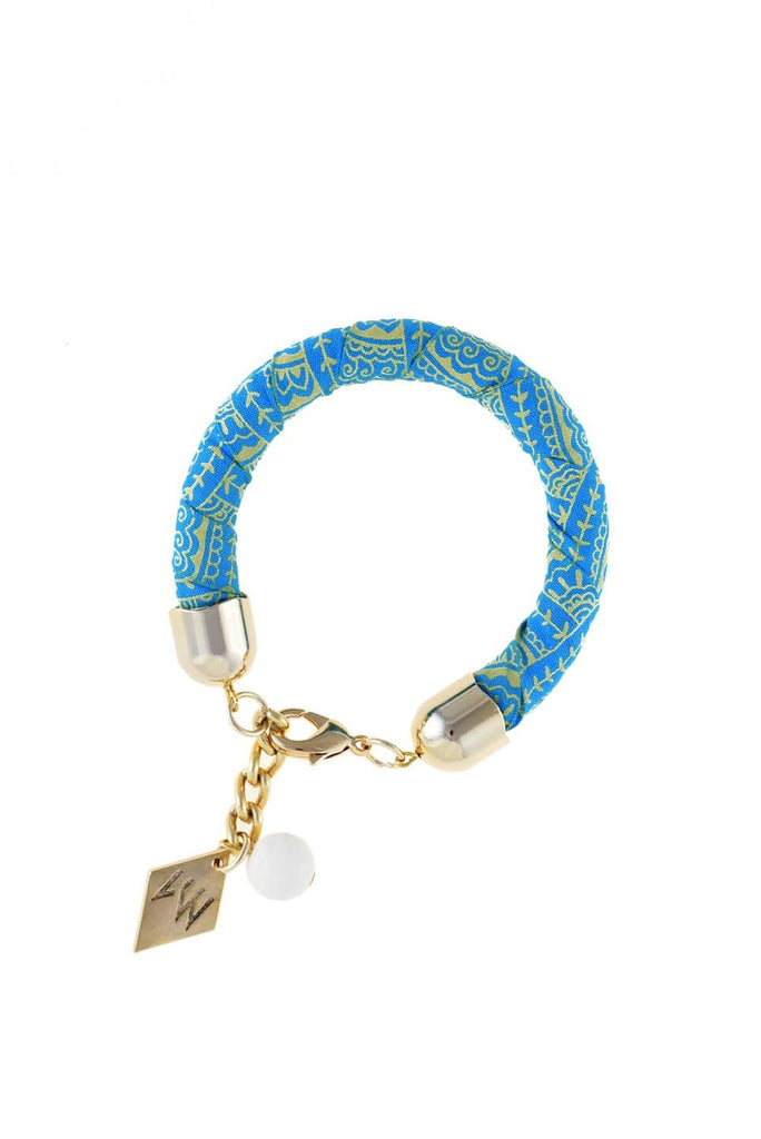 The no. 3 edition of the handcuff pattern bracelet is made of african batik cotton with galvanized metal components and white coral. Gold edition.