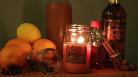 Boilo candle with ingredients.  Four queens whiskey, oranges, lemon, cinnamon, honey, star anise, nutmeg, and cloves.