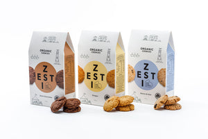 Zesti Organic Cookies 3 packs with cookies in front of packs.