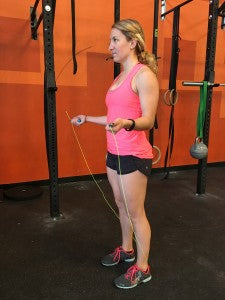 Starting position for double unders, with a relaxed grip and close elbows.