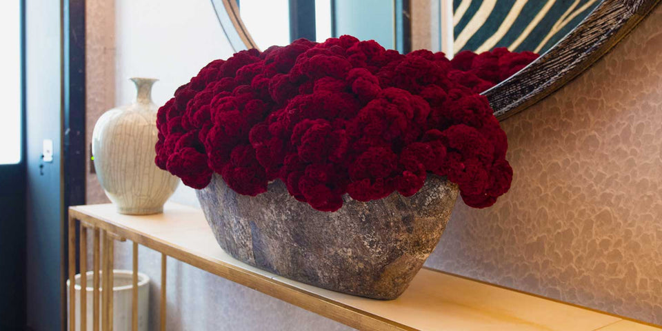 Dried burgundy celosia in boat-shaped black tub shell vessel