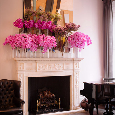 Mantel arrangements of lilac and phalaenopsis in fuchsia