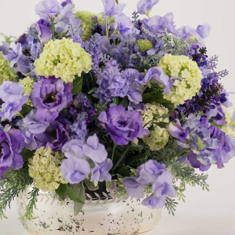 Arrangement of mixed summer silks and foliage in lilac, in mirrored container