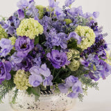 960x960**center**Arrangement of mixed summer silks and foliage in lilac, in mirrored container**enquire