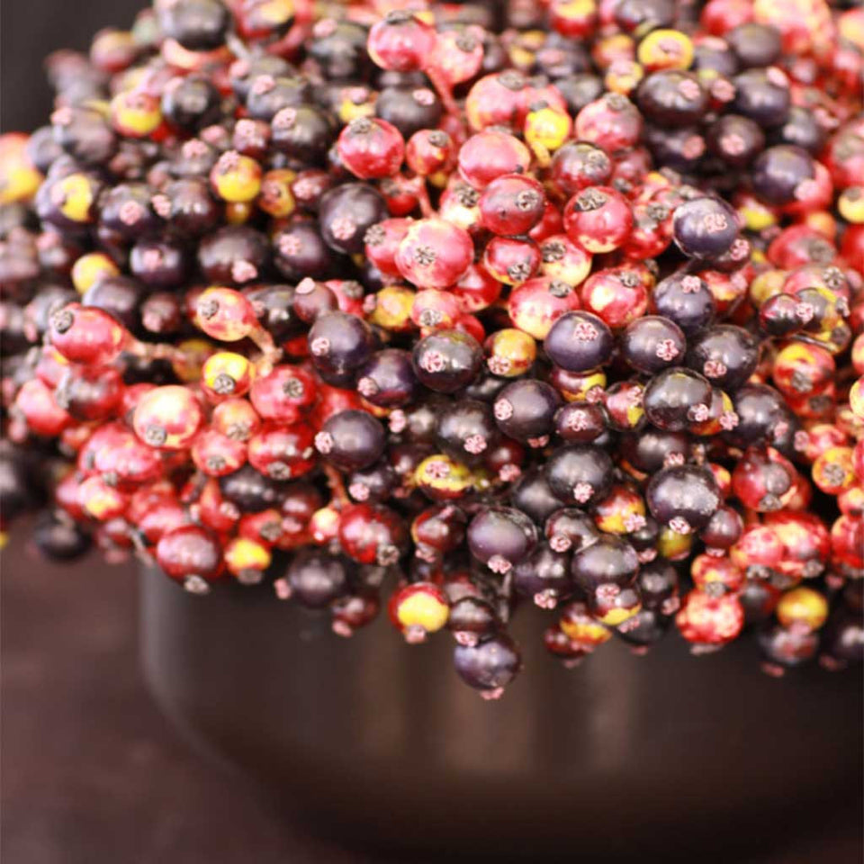 Faux autumn berries in black ceramic container