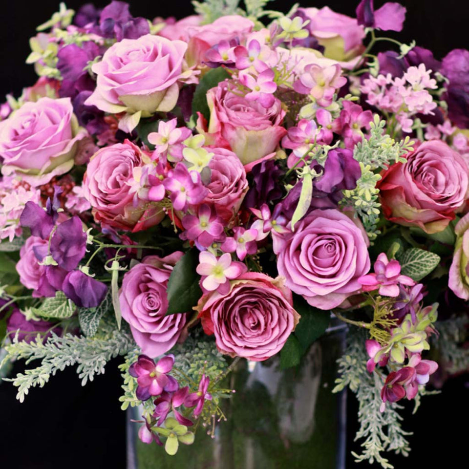 Silk arrangement of roses, sweet pea with phlox and foliage in glass container lined with moss