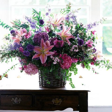 Country style arrangement of singapore lillies, hydrangeas, lisianthus and foliage in woven straw basket