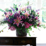 960x960**center**Country style arrangement of singapore lillies, hydrangeas, lisianthus and foliage in woven straw basket**enquire