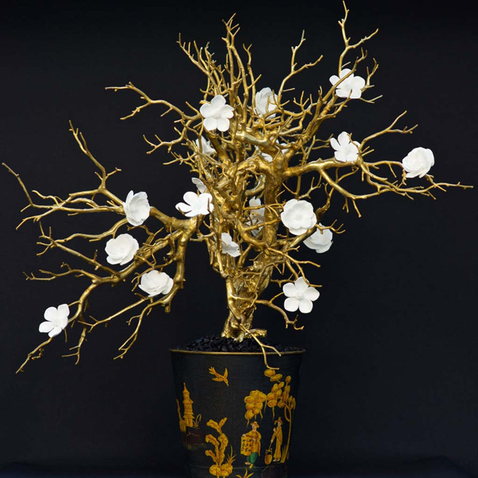 White porcelain flower on gilded branches in toleware vessel