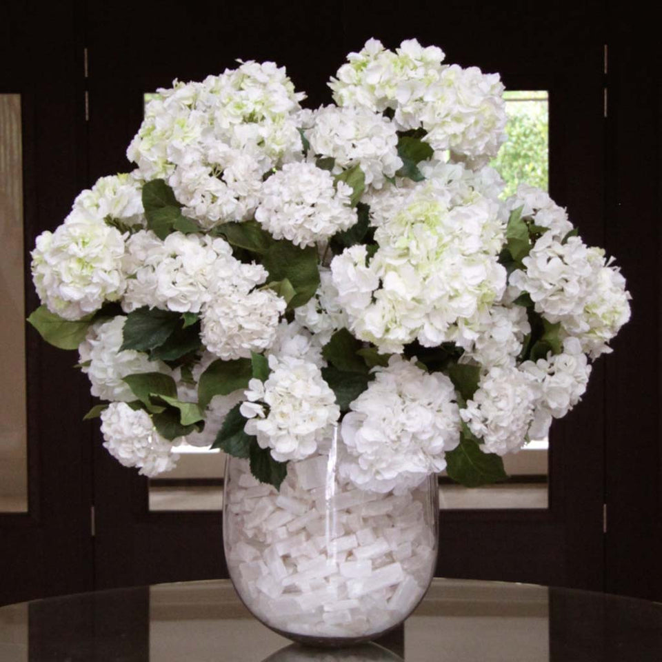 Silk hydrangeas in glass vase lined with white crystals