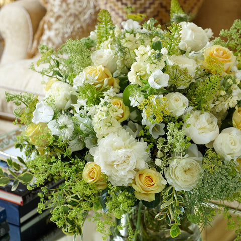 Desktop summer arrangement in natural tones with peonies, roses, phlox,and campanulas in crystal vase