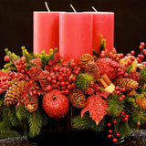 960x960**center**Large red candle arrangement with crystalised apples, faux cones, holly berries and pine**enquire
