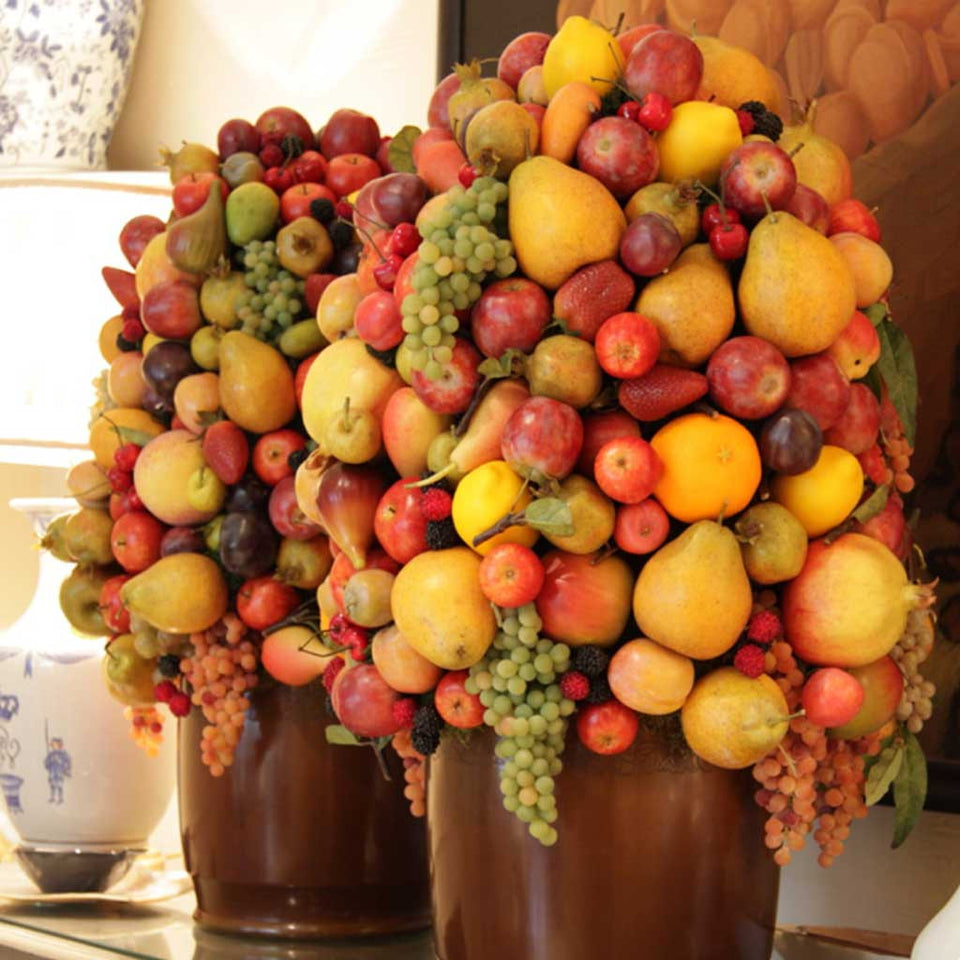 Bespoke arrangement of mixed faux fruit in brown ceramic container