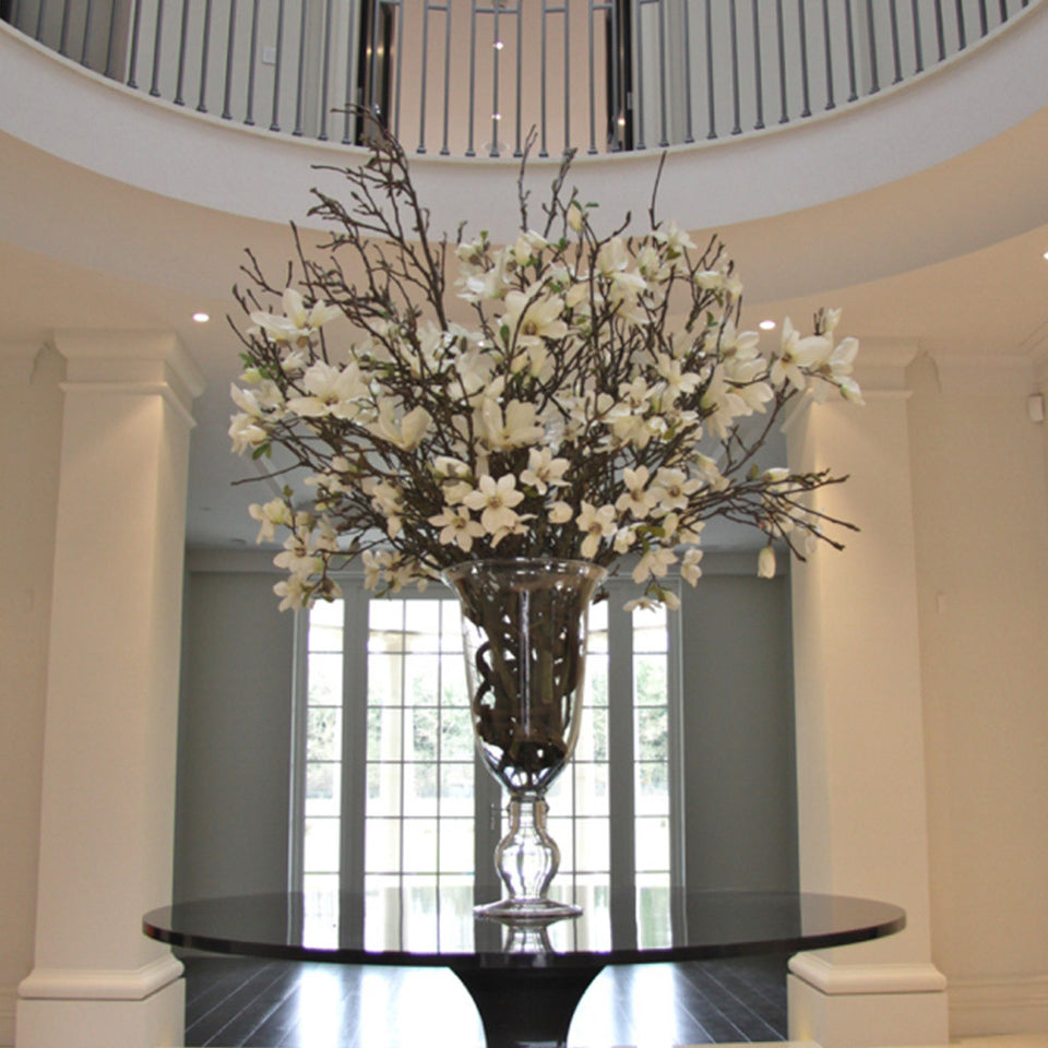 Silk magnolias arranged in glass vase in entrance hall