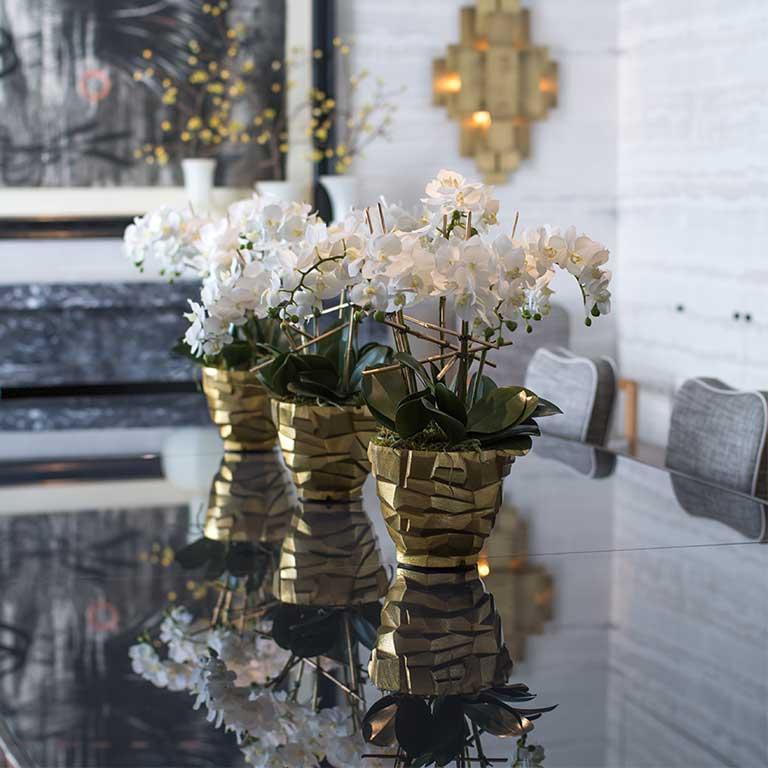 Trio of silk phalaenopsis in gold brutalist-style container