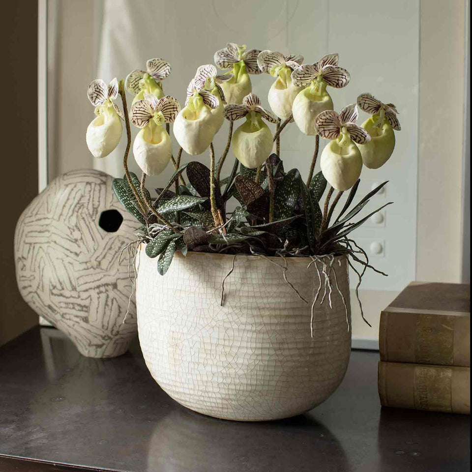 Arrangement of silk slipper orchids in oval ceramic bowl